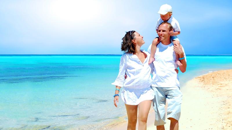 Gravid kvinna med man och barn på strand